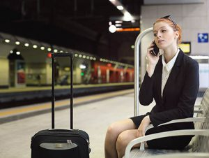 Business woman talks on smartphone while waiting for train