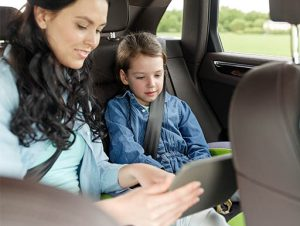 Mom sharing tablet with little girl in a car