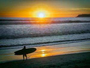 Surfer on California's Coronado Central Beach at sunset