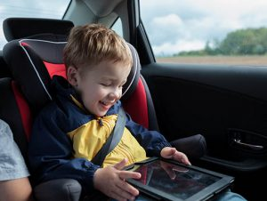 Boy in car seat interacting with tablet