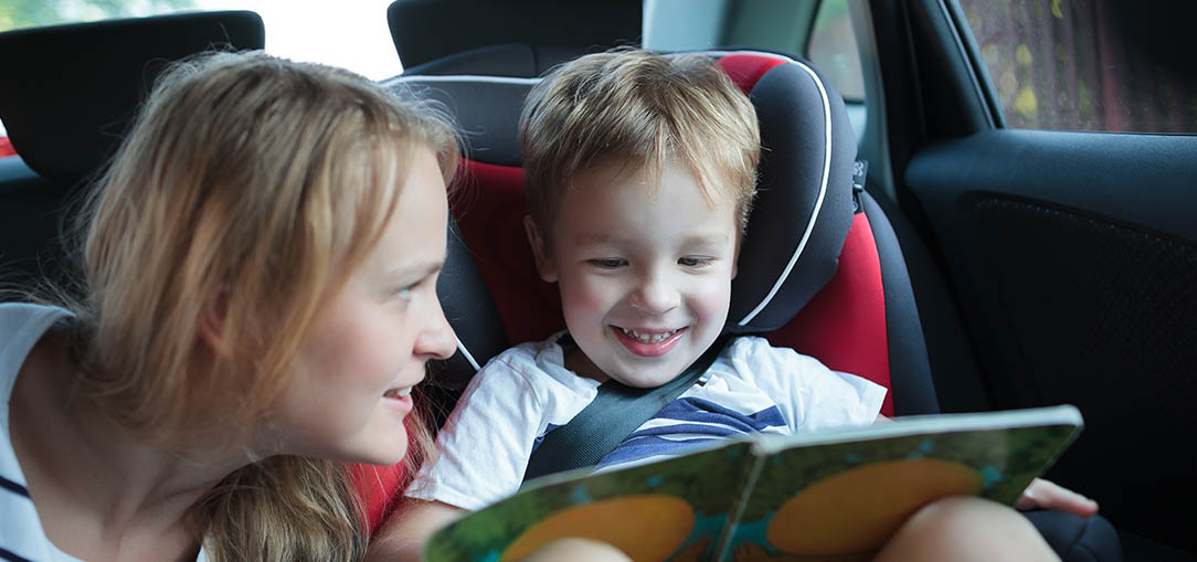 Mom reading a book to child on road trip