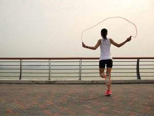 Woman skipping rope on a boardwalk