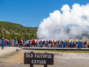 ourists viewing Old Faithful Geyser in Yellowstone National Park