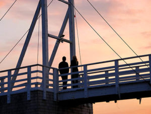 The silhouette of a couple standing on a pedestrian bridge with a gorgeous orange sunset sky behind them