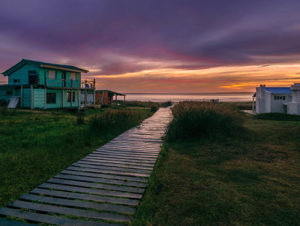 A wooden walkway surrounded by grass leads to two beach houses at sunset in Cabo Polonio in Uruguay