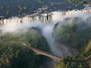 An aerial view of Victoria Falls with the large waterfall in the background and a long pedestrian bridge in the forefront