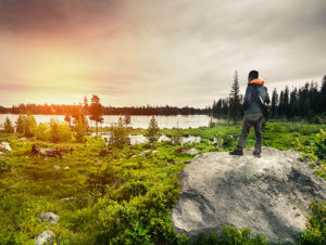 Hiker standing on rock with view of lake in Grand Teton National Park, Wyoming