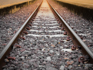 A close up of steel train tracks with rocks underneath, fading into a sunset background