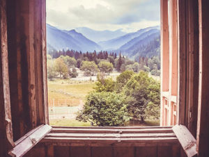 A view of mountains through a window during the summer