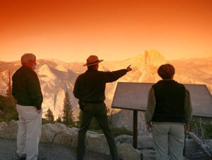 A Yosemite Park Ranger tells a story to two hikers as the sun sets in Yosemite National Park on a brisk evening.