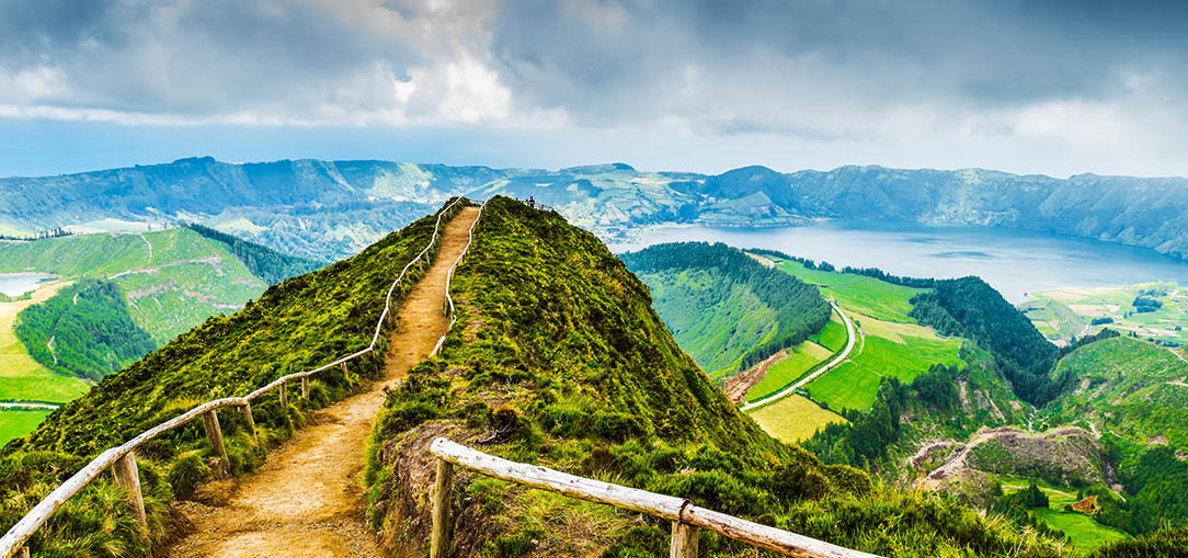 A steep walking path with railings on both sides leads to a mountain with an aerial view of rolling green hills and misty lakes