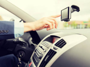 Driver is dangerously distracted from driving while interacting with GPS device mounted on windshield
