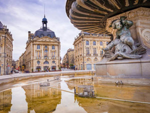 A close-up of a water fountain in Place de la Bourse in Bordeaux, France, with beautiful old buildings in the background