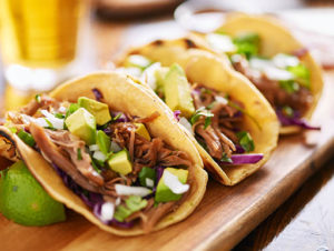 Three chicken tacos sit on a wooden board with avocado and lime on the side and a beer in the background in a restaurant in San Jose, California