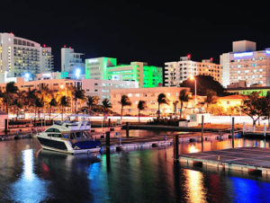 Nighttime image of the South Beach, Florida harbor with the city skyline behind it