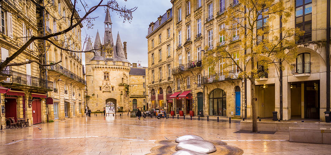 Modern art on the cream-colored marble floors in the foreground of Porte Cailhau in Bordeaux, France, with beautiful old buildings in the background