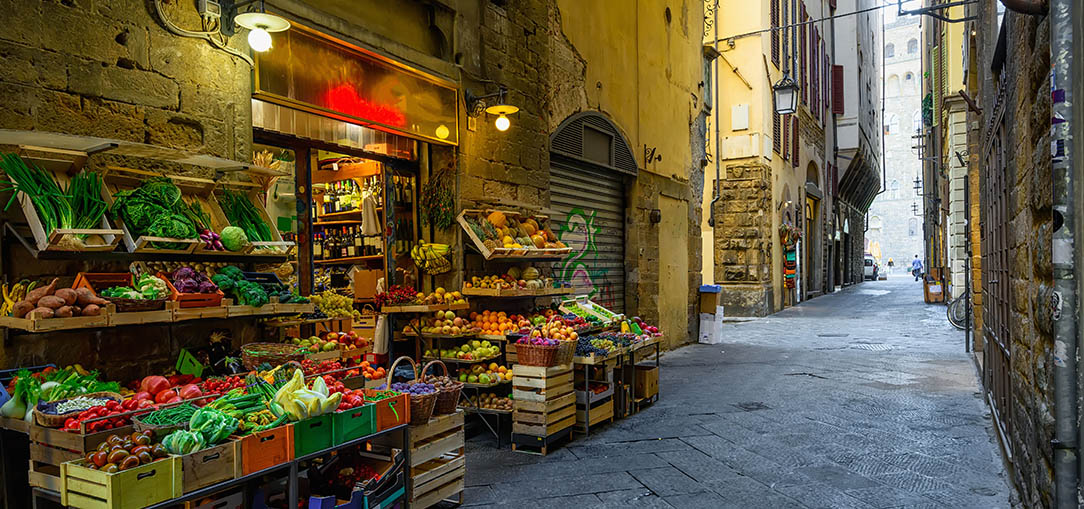 Vegetable Market features an abundance of fresh produce along a narrow street in Florence, Italy