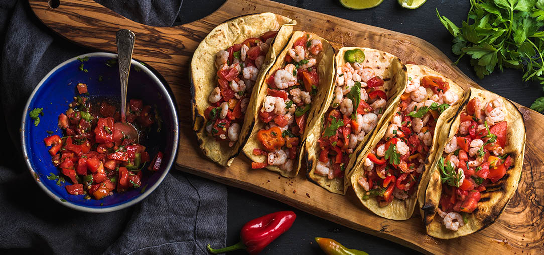 Four fresh tacos served on a wood board with lime, hot peppers and salsa in a restaurant in San Jose, California