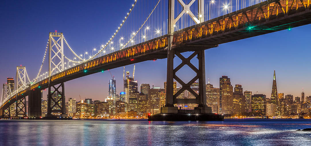 The Oakland Bay Bridge in Oakland, California, is lit up and reflected over the water at dusk