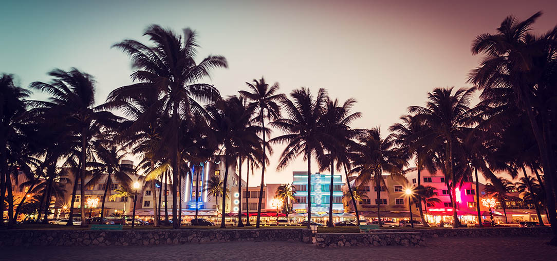 The beach at South Beach, Florida at sunset with palm trees and street lights behind it