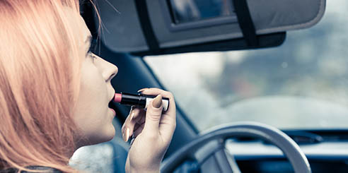 Young woman looking in the interior mirror of a car while putting on lipstick and driving.