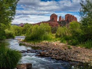 Green trees surround a calm river stream running through wilderness with Cathedral Rock in the background in Sedona, Arizona