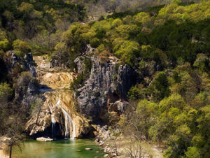 A gorgeous waterfall surrounded by green trees in Turner Falls Park in Oklahoma