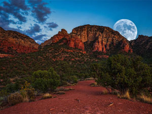 A view of supermoon from behind red and brown mountains on a hiking trail in Sedona, Arizona