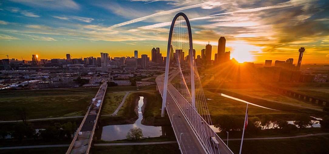 Freeways leading into and out of Dallas, Texas, with the skyline of the city in the background against a beautiful sunset