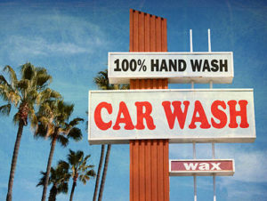 A sign for a car wash business that offers 100% hand wash and car waxing services