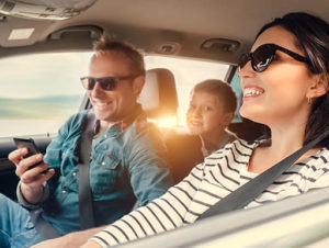 A young smiling mom driving the car while the father sits in the passenger seat looking at his phone and a young boy peeks his out in the middle of the parents from the back seat while on a road trip