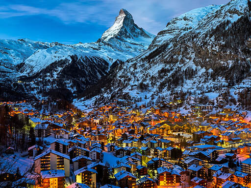 An aerial view at dawn of the glowing lights from the town of Zermatt, and the Matterhorn mountain in Switzerland