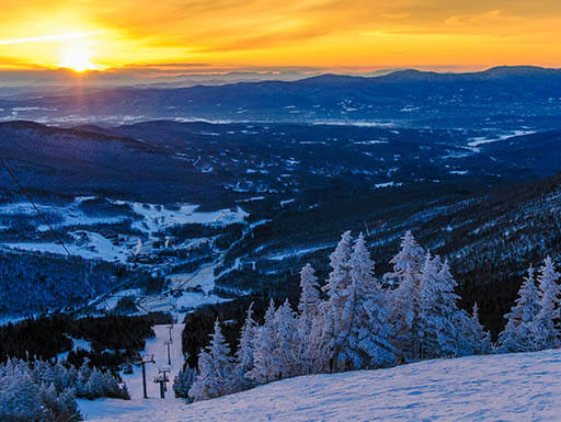 A view of Vermont's tallest mountain, Mount Mansfield with snow capped trees and ski lift at sunrise