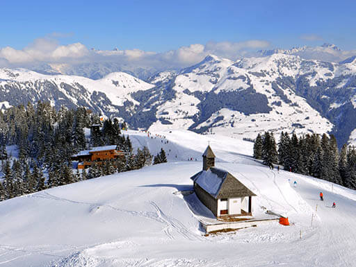 An aerial view of a historical church in the wintry mountains of Kitzbuhel, Austria on a sunny day