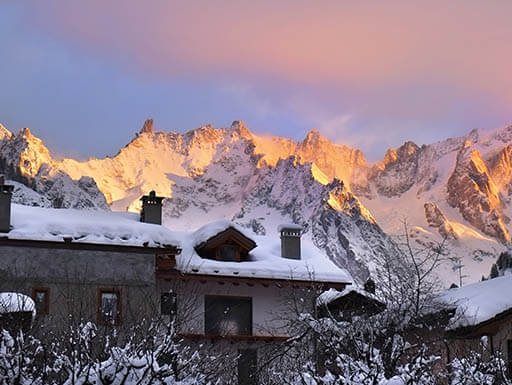 Sunrise illuminates the mountain range behind a ski resort in Courmayeur, Italy
