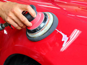 A man uses a motorized buffer with a cotton applicator pad to apply wax that will give the car a perfect glossy