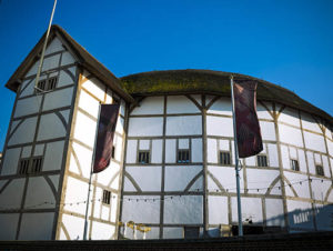 The brown and white exterior of the Globe Theatre in London, UK, with a bright blue sky behind it