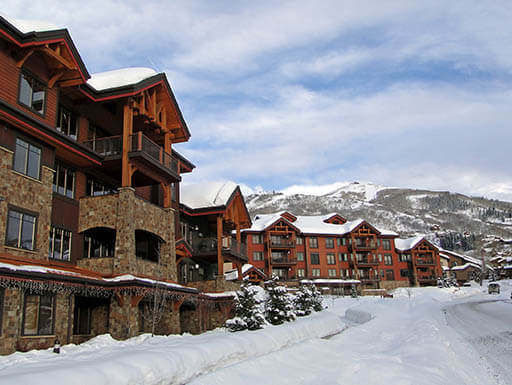 Western-style condominiums line a snowy road at the Steamboat Springs Ski Resort in Colorado