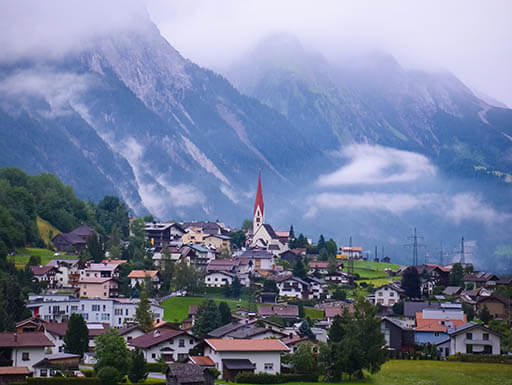 The Arlberg mountain range towers higher than the clouds in the ski resort town of St Anton am Arlberg in Austria