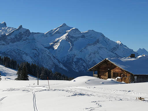 Fresh tracks in the snow lead skiers to a rustic cabin with a mountain view near the ski resort town of Gstaad, Switzerland