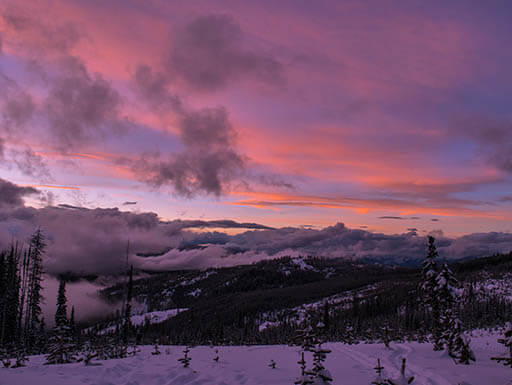 A snowy mountain landscape in Rossland, British Columbia in Canada reflects the pinks and purples of a gorgeous sunset