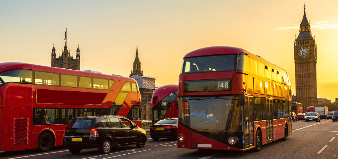 Red double decker buses driving in streets of London at dusk with Big Ben behind them