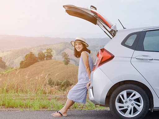 Young woman leaning against silver car with grassy hills in the background.