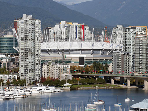 Boats sit in the harbor of Vancouver, Canada surrounded by tall white skyscrapers and city buildings, with mountains in the background