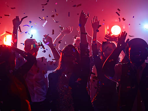 Party-goers dance in a live music venue with confetti falling down on them and bright red lights beaming from behind