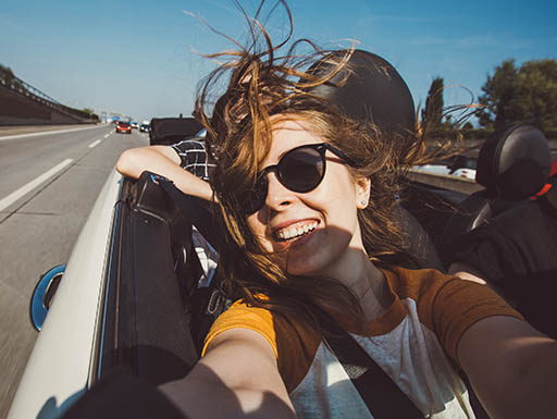 Young woman taking selfie in a convertible under a blue sky while on a road trip.