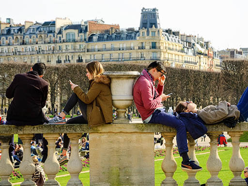 Visitors taking a break from sightseeing in Luxembourg Gardens in Paris