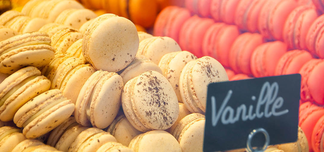 Close up of white, pink, and orange macarons in a display case