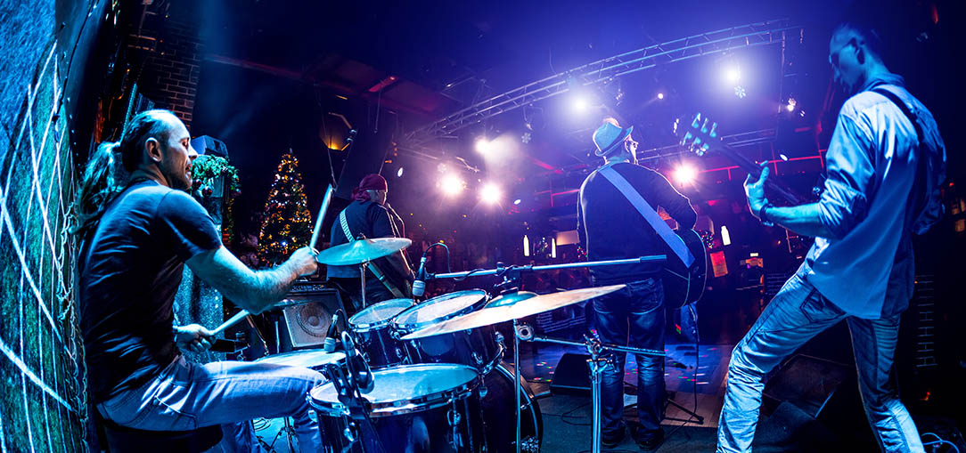 A fish eye camera lens captures a drummer, guitar player and singer on stage from behind in a small music venue in Vancouver, Canada