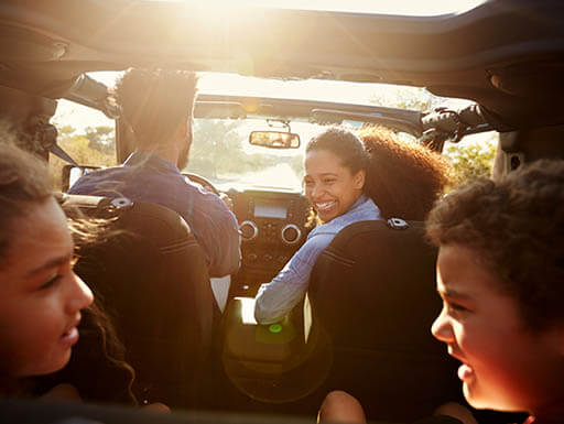 Two young children smile at each other in the foreground as they sit in the back of a vehicle on a roadtrip, with dad driving in the background and mom in the passenger seat smiling back at the kids
